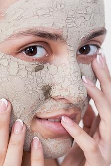 顔のマスクを持つ極端なクローズアップ女性