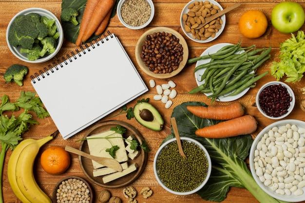 野菜とノートブックモックアップのトップビューの配置