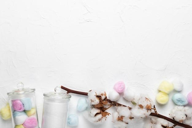 綿の枝とテーブルの上の瓶