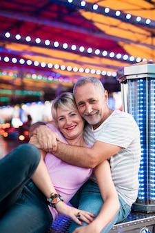 テーマパークでポーズをとって幸せなカップル