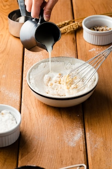 Высокий угол руки наливая молоко в миску