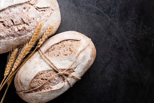 黒の背景にパンと小麦のトップビュー