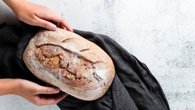 布の上のパンを保持している手のフラットレイアウト
