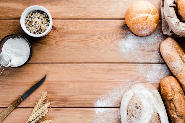 木製の背景にパンのフラットレイアウト
