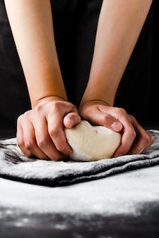Вид спереди руки и тесто с черным фоном