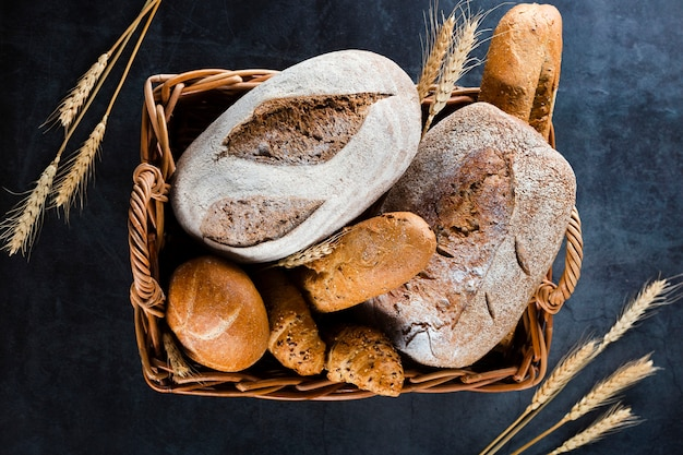黒いテーブルの上のバスケットにパンのトップビュー