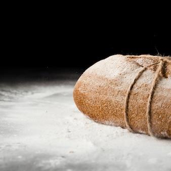 黒の背景にパンと小麦粉のクローズアップビュー