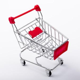 無地の背景にショッピングカートのクローズアップ
