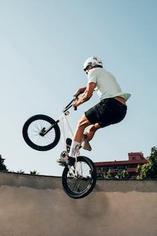 若い男が自転車で極端なジャンプ