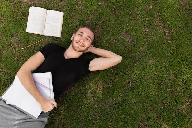 Студент университета отдыхает на траве
