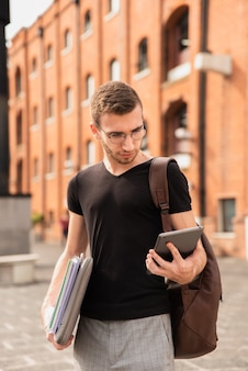 彼のタブレットを見て、彼のノートを保持している男
