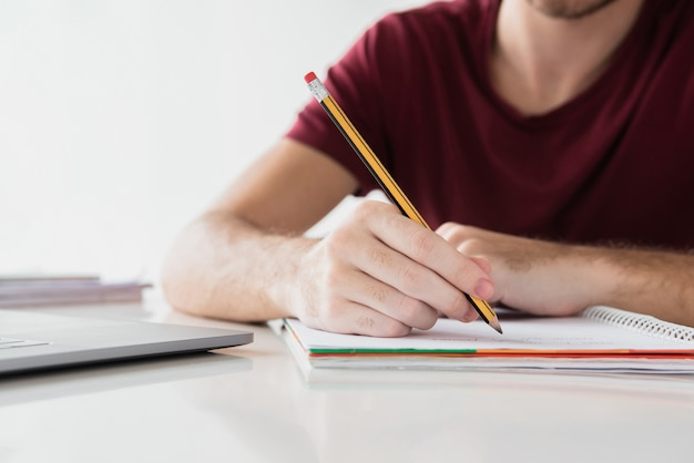 鉛筆で彼のメモ帳に書いているその男