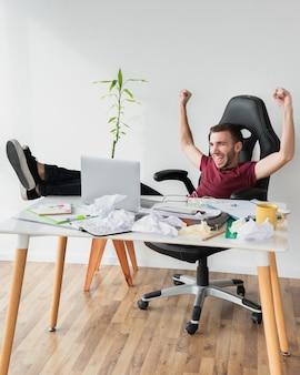 Человек, показывая победу и сидя на игровом стуле