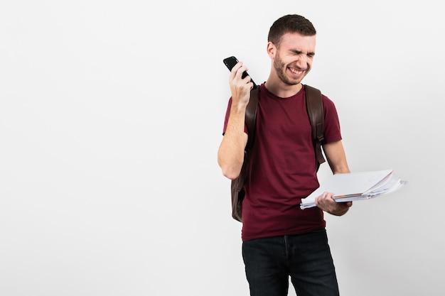 Парень смеется и держит свой телефон