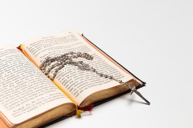 Крупным планом открытая священная книга с ожерельем