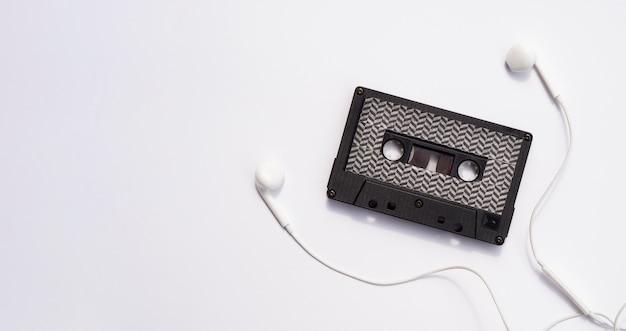 イヤホンとコピースペースが付いた黒いカセットテープ