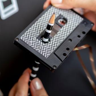 クローズアップショット人の鉛筆でカセットテープを修復