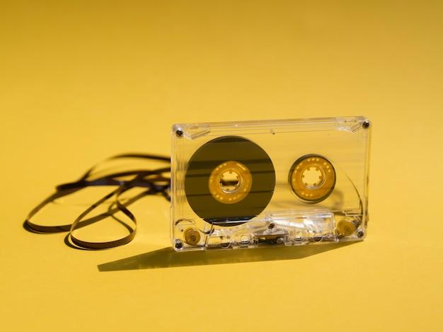 Прозрачная сломанная кассета на желтом фоне