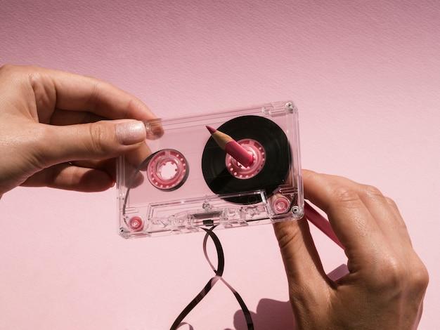 ピンクの鉛筆で壊れたカセットテープを修復する女性