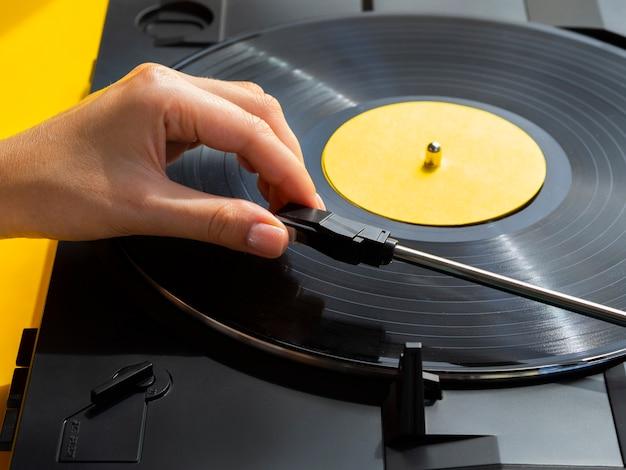 プレーヤーにビニールレコードを置く人