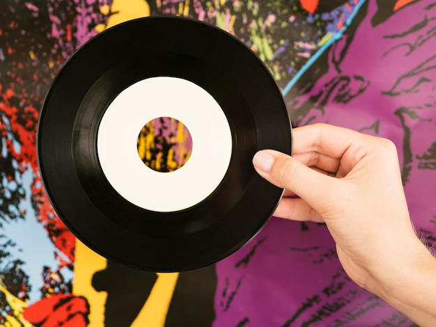 Лицо, занимающее виниловый диск в стиле ретро возле разноцветного обоя