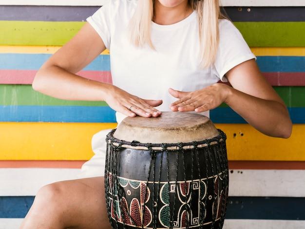 Молодая женщина играет на барабане юкера
