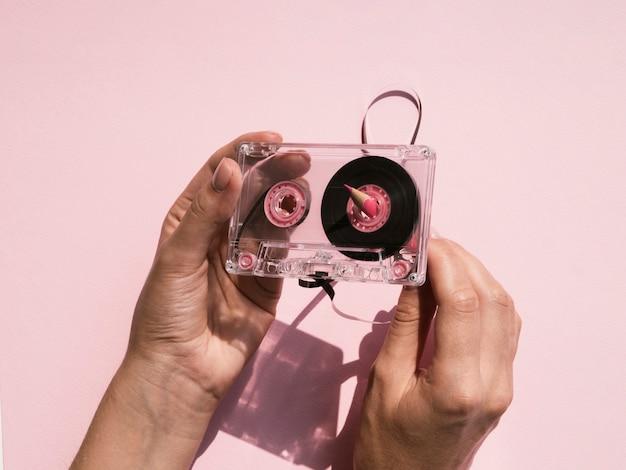透明なカセットテープを固定する人