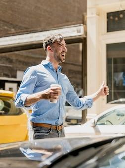 コーヒーを飲みながらタクシーを選ぶ若い男