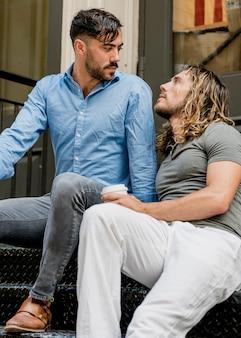 Двое друзей-мужчин сидят на лестнице