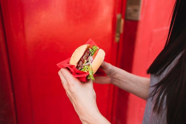 Крупным планом женщина, держащая вкусный гамбургер