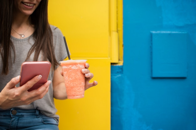 デバイスとジュースを持つクローズアップ女性