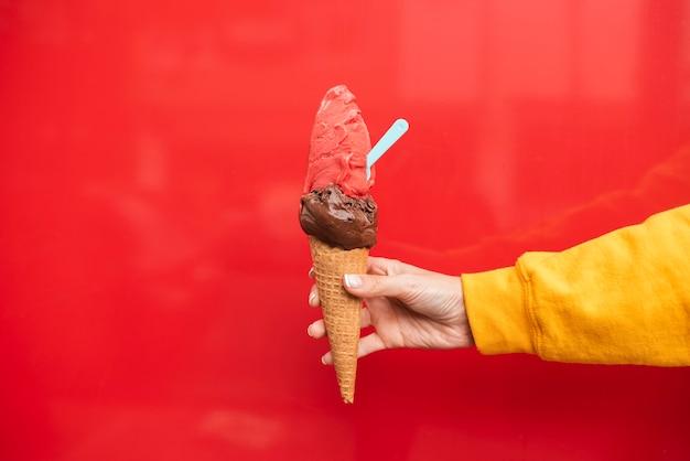 アイスクリームを保持しているクローズアップの人