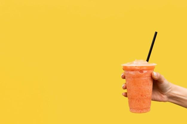 Крупным планом рука держит напиток с желтым фоном