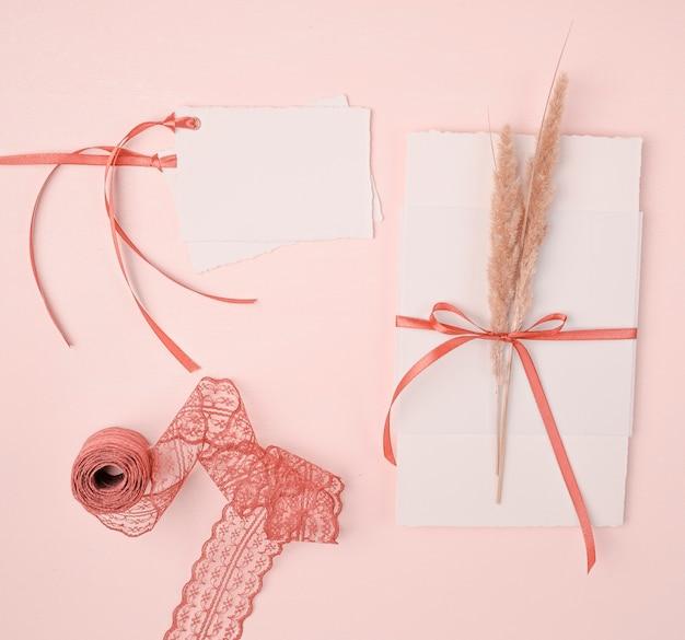 ピンクの背景の結婚式招待状のトップビューの乙女チックな配置