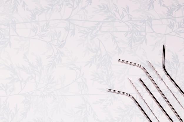 Металлические соломинки на фоне с листьями