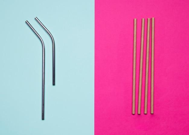 Металлические и бумажные соломинки на двухцветном фоне