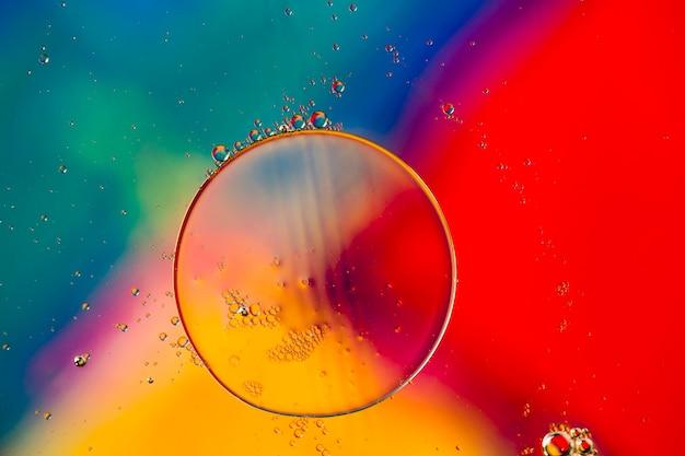 クローズアップの油性泡とカラフルな水の背景の液滴