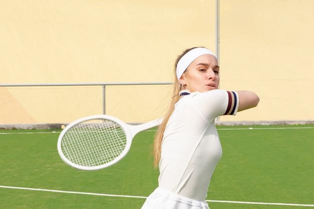 若いテニス選手がボールを打つ