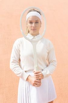 テニスラケットで顔を覆っている遊び心のある女性