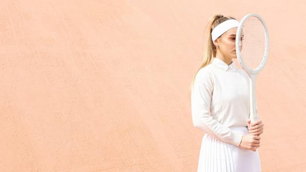 ラケットで顔を覆っている若いテニス選手