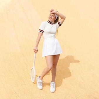 カメラにポーズスマイリー女性テニスプレーヤー