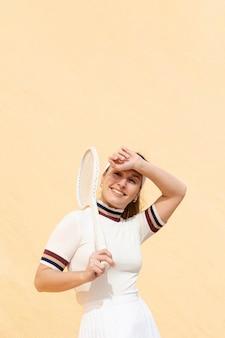 Молодой спортсмен держит теннисную ракетку на плече