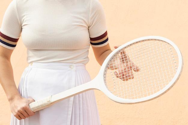 Теннисистка держит ракетку на поле