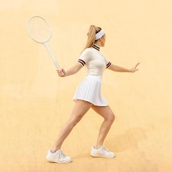 若いテニスプレーヤーの位置を打つ