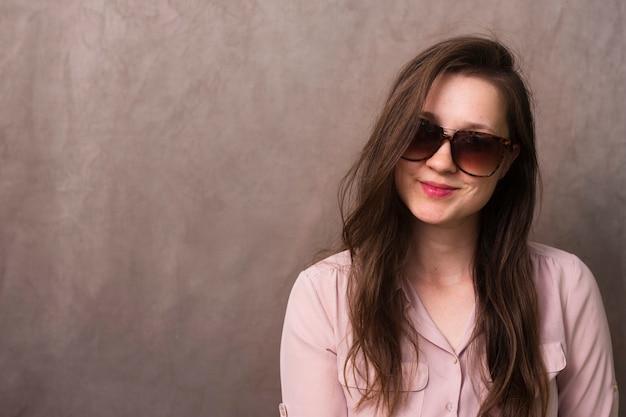 正面のサングラスを持つ美しい女性