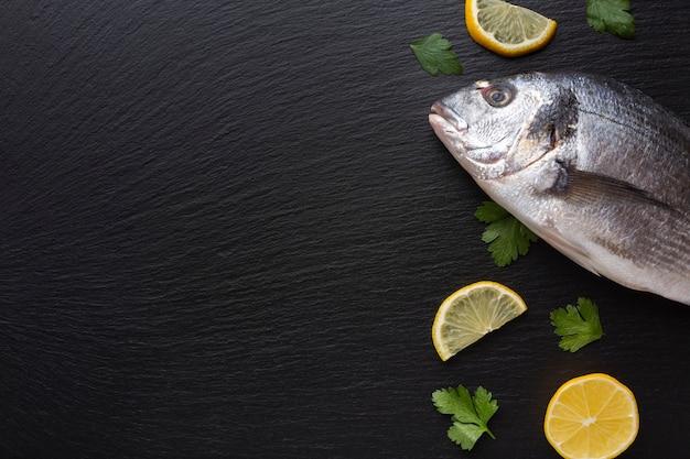 Вид сверху свежей рыбы с лимонами