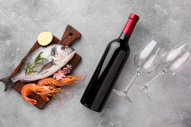 Вид сверху свежей рыбы и бутылка вина