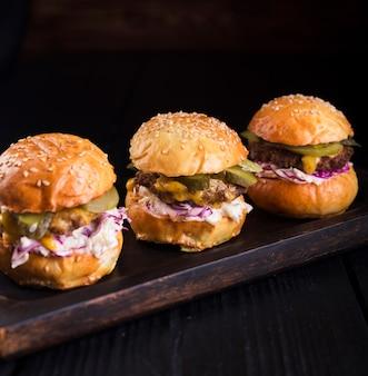 Набор вкусных гамбургеров на деревянной доске