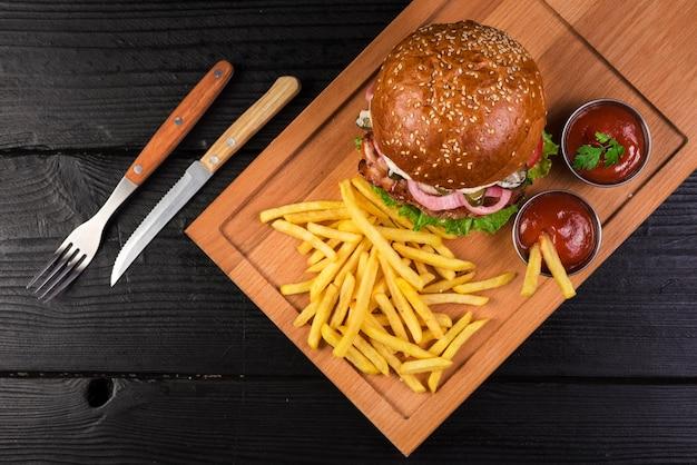 フライドポテトとケチャップソースが付いたハイアングルビーフバーガー