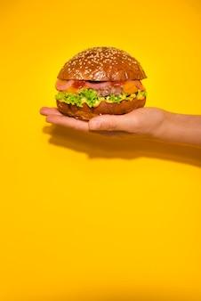 Рука держит классический говяжий бургер с листьями салата